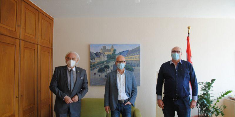 Das Bild zeigt den Hans Mayer, Dirk Meid und Hermann Wagner mit aufgesetzten Masken und Abstand in einer Reihe im Büro des Oberbürgermeisters stehend. Im Hintergrund hängt ein Gemälde der Genovevaburg.